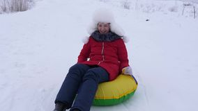 多雪的板材的女孩从高多雪的山和笑滚动下来高兴地 少年在与雪撬的冬天使用 股票录像