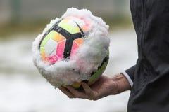 多雪的足球和裁判员` s手特写镜头  库存照片