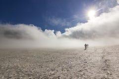 多雪的领域的两个人在与上面云彩和天空的堪察加山 免版税库存照片