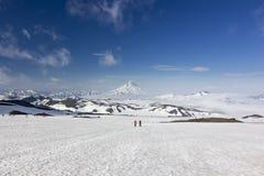 多雪的领域的两个人在雪火山近盖的堪察加山 库存图片