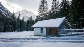 多雪的高山谷的山房子 库存照片