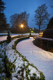 多雪黄昏的规则式园林 免版税库存照片