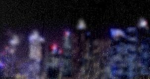 夜下雨倒下在玻璃窗的下落有多颜色光bokeh摩天大楼城市背景,水滴 皇族释放例证