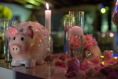 夜与蜡烛、piggybank和花的婚礼装饰 免版税图库摄影