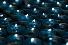 夜光 被点燃的茶光蜡烛在与蓝色的银的晚上 免版税库存图片