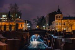 夜冬天沃罗涅日,在路的汽车移动在石桥梁下 库存图片