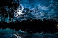 夜可怕场面 在池塘上的满月有树的剪影的 免版税图库摄影