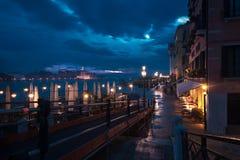 夜在威尼斯,渠道的露台在有启发性大厦和江边的背景 免版税库存照片