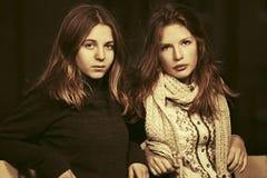 夜城市街道的两个年轻时尚女孩 免版税库存图片
