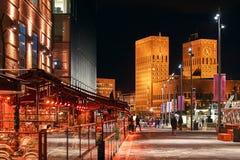 夜奥斯陆城市视图、挪威Aker Brygge船坞的有餐馆的和香港大会堂或者Radhuset在背景 库存图片