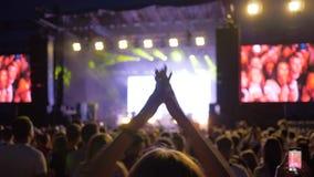 夜娱乐,跳跃和拍手在人群人的活跃爱好者女孩在与明亮地点燃的岩石生活音乐会 股票视频