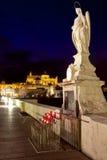 夜射击了天使在罗马桥梁的Raphael雕象在科多巴,安大路西亚 库存图片