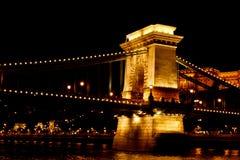 夜布达佩斯,发光在金子 在多瑙河的铁锁式桥梁由电灯泡照亮 从河的照片 免版税库存图片