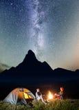 夜帐篷野营 旅游夫妇-坐由篝火的女孩和人在难以置信地美丽的满天星斗的天空下 库存图片