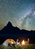 夜帐篷野营 旅游家庭-坐由篝火的男人和妇女在难以置信地美丽的满天星斗的天空下 库存照片