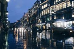 夜根据街灯的城市街道和汽车发光红色的车灯白色和 沥青纹理射击关闭 免版税库存照片