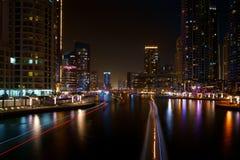 夜河交通长的追踪者在迪拜阿拉伯联合酋长国沿有五颜六色的反射和被弄脏的smok的一条城市河集中 库存图片