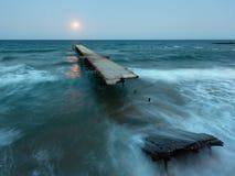 夜海海浪、被破坏的码头和月亮在天空(黑海,保加利亚 免版税库存照片