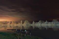 夜渔,鲤鱼标尺,在湖的Cloudscape反射 免版税库存照片