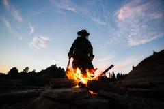 夜现出轮廓拿着火的女性人木棍子由森林 库存照片