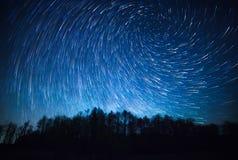 夜空、螺旋星足迹和森林 免版税库存图片
