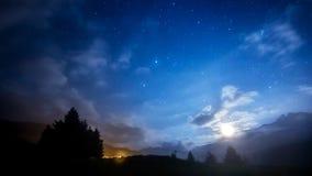 夜空星、月亮和云彩横跨山 免版税库存照片