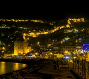 夜老城市的视图图象在海附近的有古老城堡、房子和石墙风景的在光之间从阿拉尼亚安塔利亚Turke 库存照片