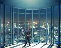 夜观点的大厦和人从玻璃窗 免版税库存照片