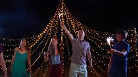 夜跳舞与闪烁发光物的海滩党和朋友 影视素材