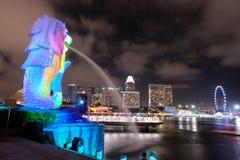夜轻的Merlion有城市视图 图库摄影