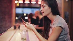 夜酒吧的美女讲话与智能手机,听的语音留言 享受夜生活一会儿的妇女 股票录像