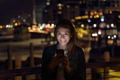夜间使用她的智能手机的年轻女人 作为背景的城市光 免版税库存照片