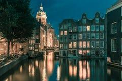 夜阿姆斯特丹运河、教会和桥梁 库存照片