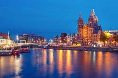夜阿姆斯特丹运河和大教堂圣尼古拉 库存照片