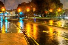 夜雨视图黄色在英国环形交通枢纽的红绿灯 免版税库存照片