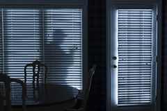 夜贼Sneeking剪影由后门决定的在晚上 免版税库存照片