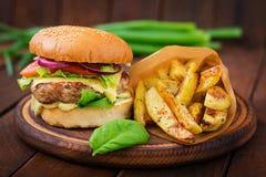 大三明治-汉堡包用水多的牛肉汉堡、乳酪、蕃茄和红洋葱 免版税库存图片