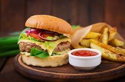 大三明治-汉堡包用水多的牛肉汉堡、乳酪、蕃茄和红洋葱 免版税库存照片