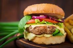大三明治-汉堡包用水多的牛肉汉堡、乳酪、蕃茄和红洋葱 库存图片