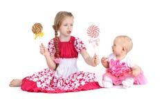 大两个的姐妹8年和11个月用糖果 图库摄影