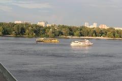 大两白色和有人的黄色船沿Dnieper德聂伯级,Dnipro,基辅,乌克兰在船上去 在河的桥梁 库存照片