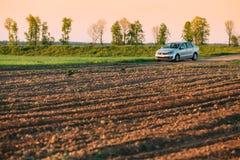 大众波罗在麦田的汽车停车处 日落在麦田的日出天空 免版税库存图片
