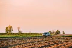 大众波罗在麦田的汽车停车处 日落日出天空 图库摄影