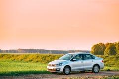 大众波罗在麦田的汽车停车处 日落日出天空O 免版税库存图片