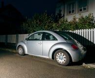 大众甲壳虫在晚上在房子附近的城市 免版税库存图片