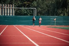 大体育场操刀与篱芭和两个赛跑者 免版税库存照片