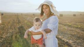 大使用与领域的男婴的帽子和轻量级礼服的可爱的年轻母亲与大包 有一点的妈妈 影视素材