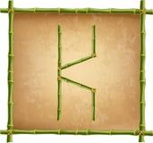 大写字母K做了绿色竹棍子在老纸背景 皇族释放例证