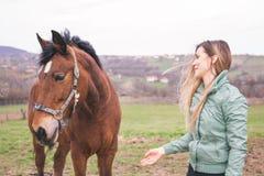 大农场的美丽的少妇有一匹棕色马的 免版税库存照片