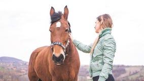 大农场的美丽的少妇有一匹棕色马的 免版税图库摄影